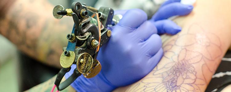 機械で入れ墨を彫る男性